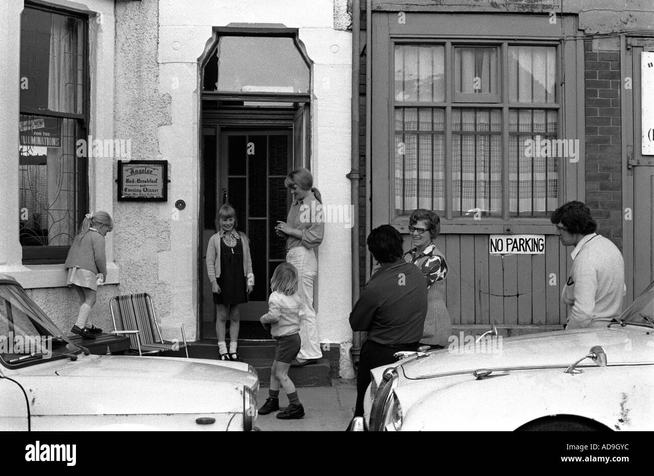 Families talk and children play outside their bed and breakfast hotel. Blackpool, Lancashire  England. 1974 1970s UK HOMER SYKES - Stock Image