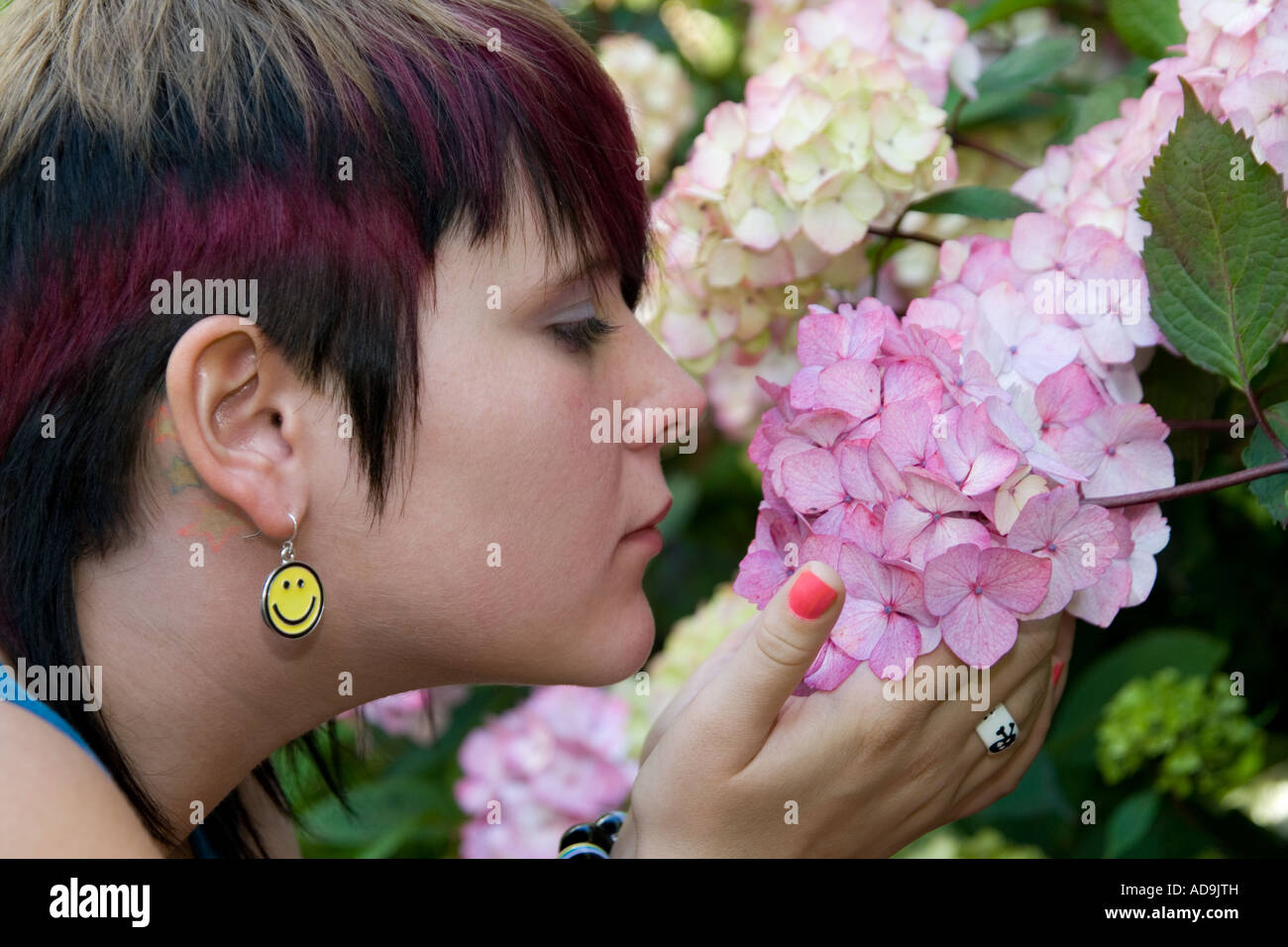 "Woman wearing ""smiley face earrings"" smelling pink flowers inside the Dundee University Botanical Gardens, UK Stock Photo"