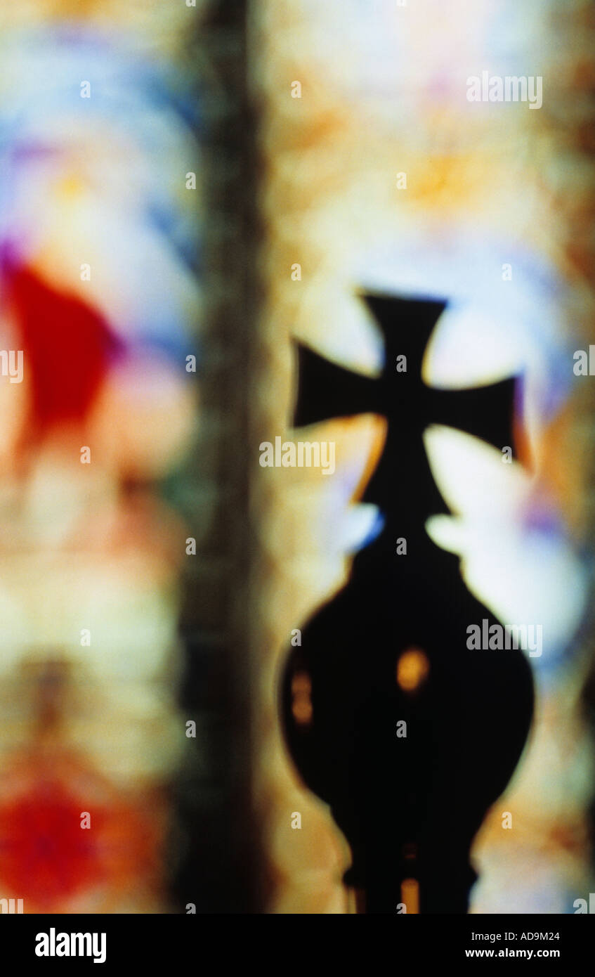 Close up of a brass cross surmounting an orb and silhouetted against distant stained glass church windows - Stock Image