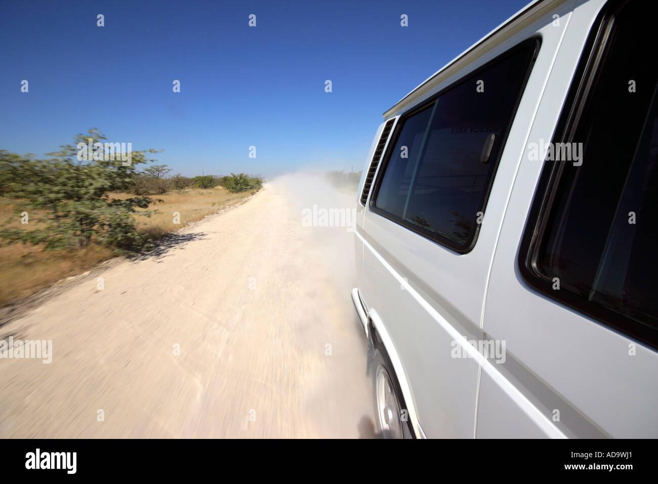 e3c881dc24 White minibus traveling down gravel road in Namibia - Stock Image
