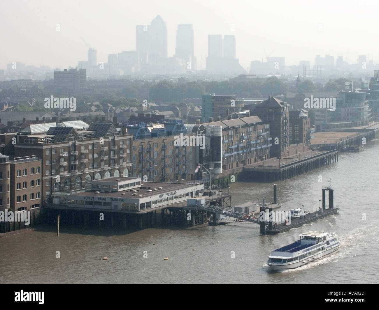 High level view over river Thames and east London with Canary Wharf docklands landmark skyscrapers shrouded in haze Tower Hamlets London England UK - Stock Image