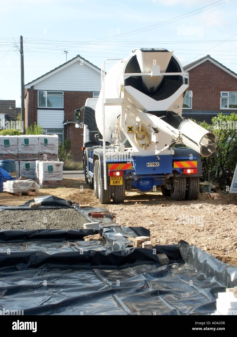 Concrete cement mixer delivery lorry truck reverse onto construction building site to pour more concrete on plastic damp proof membrane England UK - Stock Image