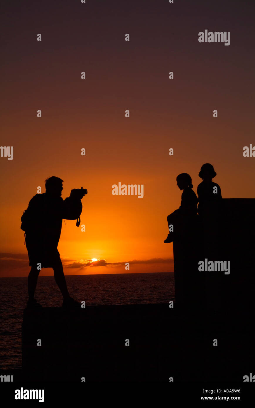 father taking picture of two sons in the sunset - Stock Image