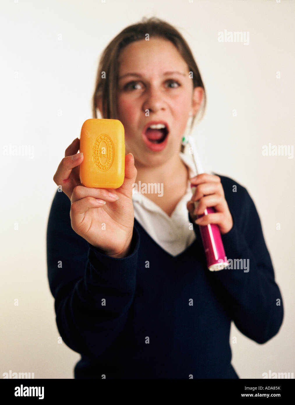 Portrait of girl holding soap and toothbrush - Stock Image
