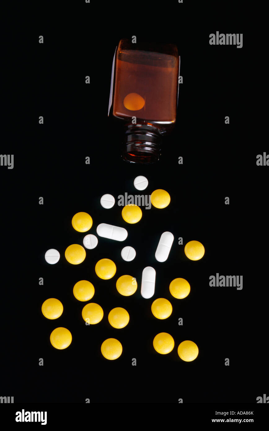 Pills with bottle on black background - Stock Image
