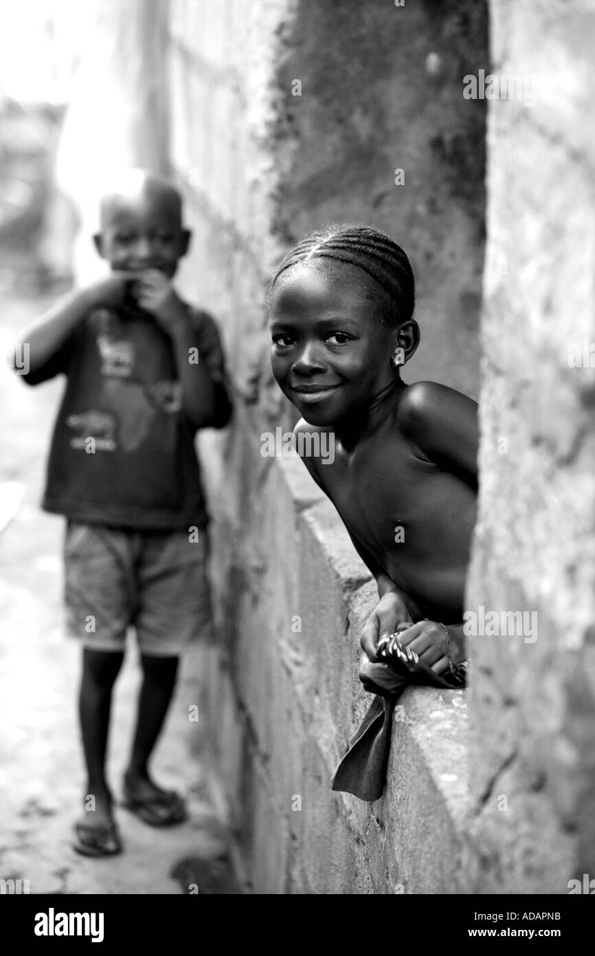 Vertical black and white portrait of two children in street in sierra leone smiling at camera freetown west africa