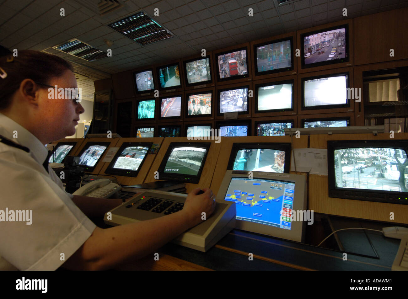 A CCTV operator at Brighton police station controls a bank of screens from CCTV cameras monitoring the streets of the city - Stock Image