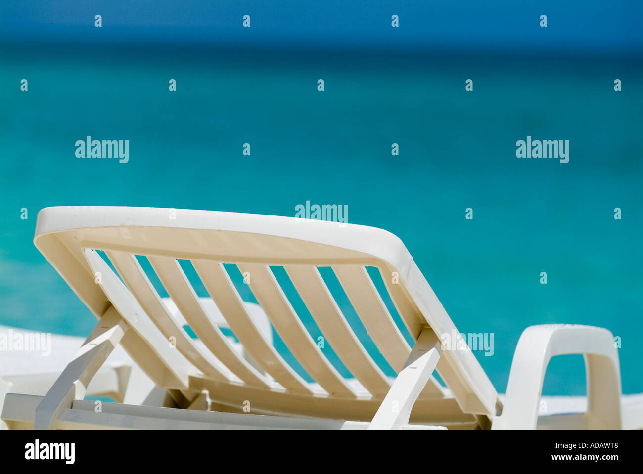 Empty white deck chair / sun lounger on a tropical beach with bright blue ocean - Stock Image