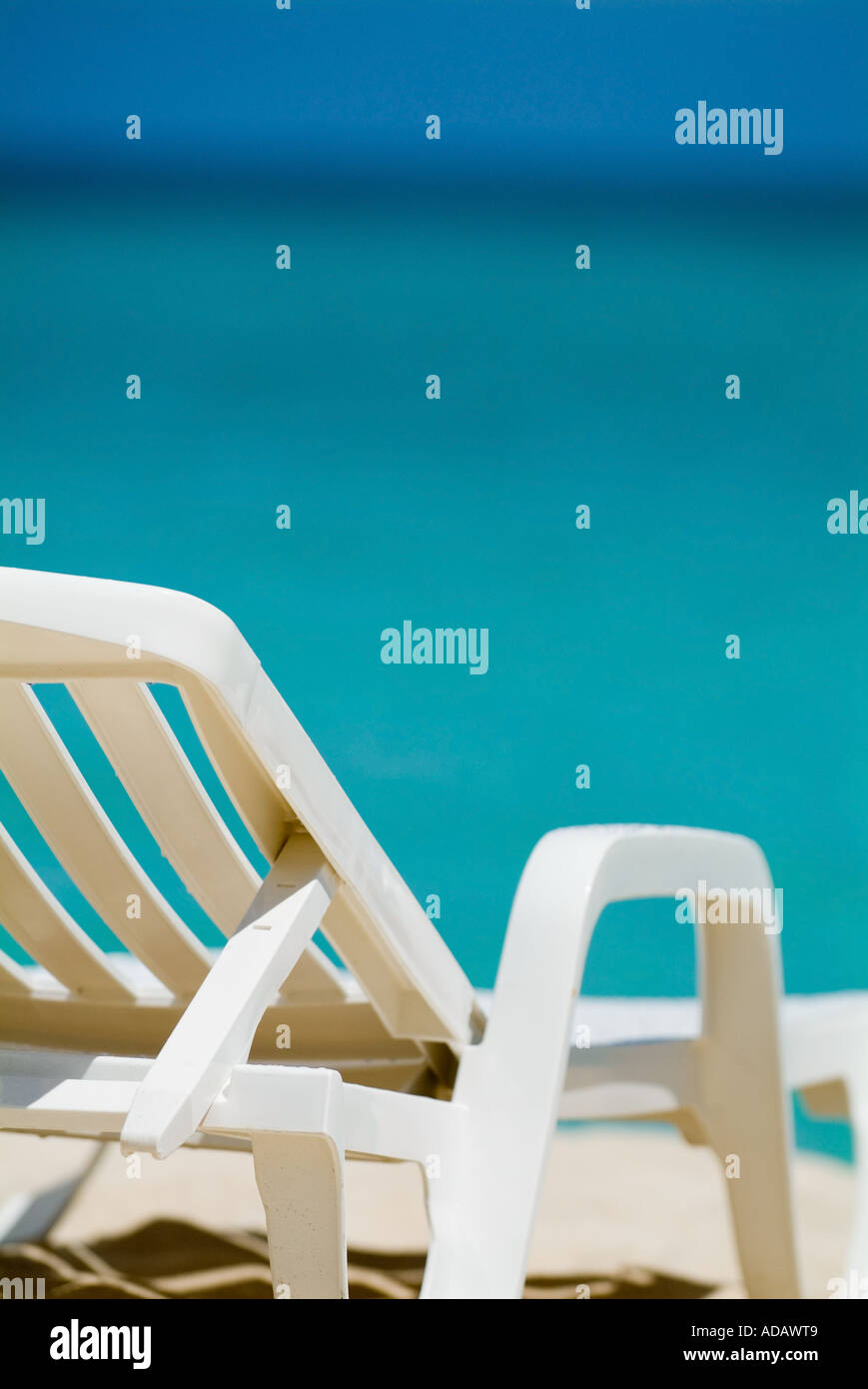 Empty white deck chair on a tropical beach with bright blue sea waters - Stock Image