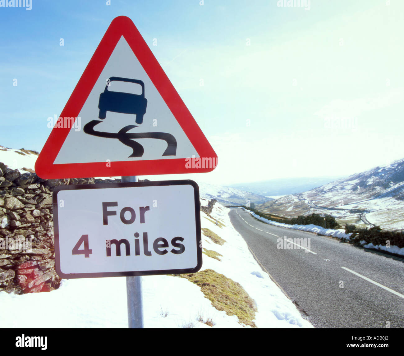 Slippery roads surface sign at the summit of the Kirkstone Pass, Lake District, United Kingdom. - Stock Image