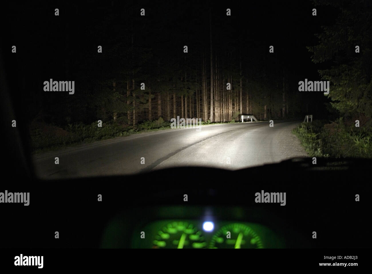 Drivers View from the Interior of a Car Driving at Night Along an Isolated Rural Road - Stock Image