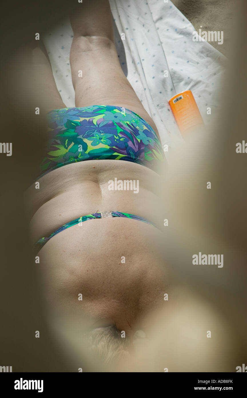 Overweight sunbather on beach Stock Photo