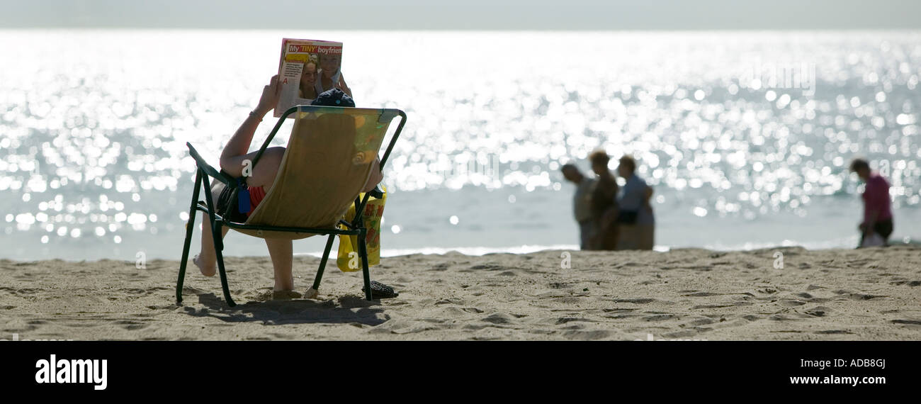 Woman on Benidorm beach reading magazine with headline My tiny boyfriend - Stock Image