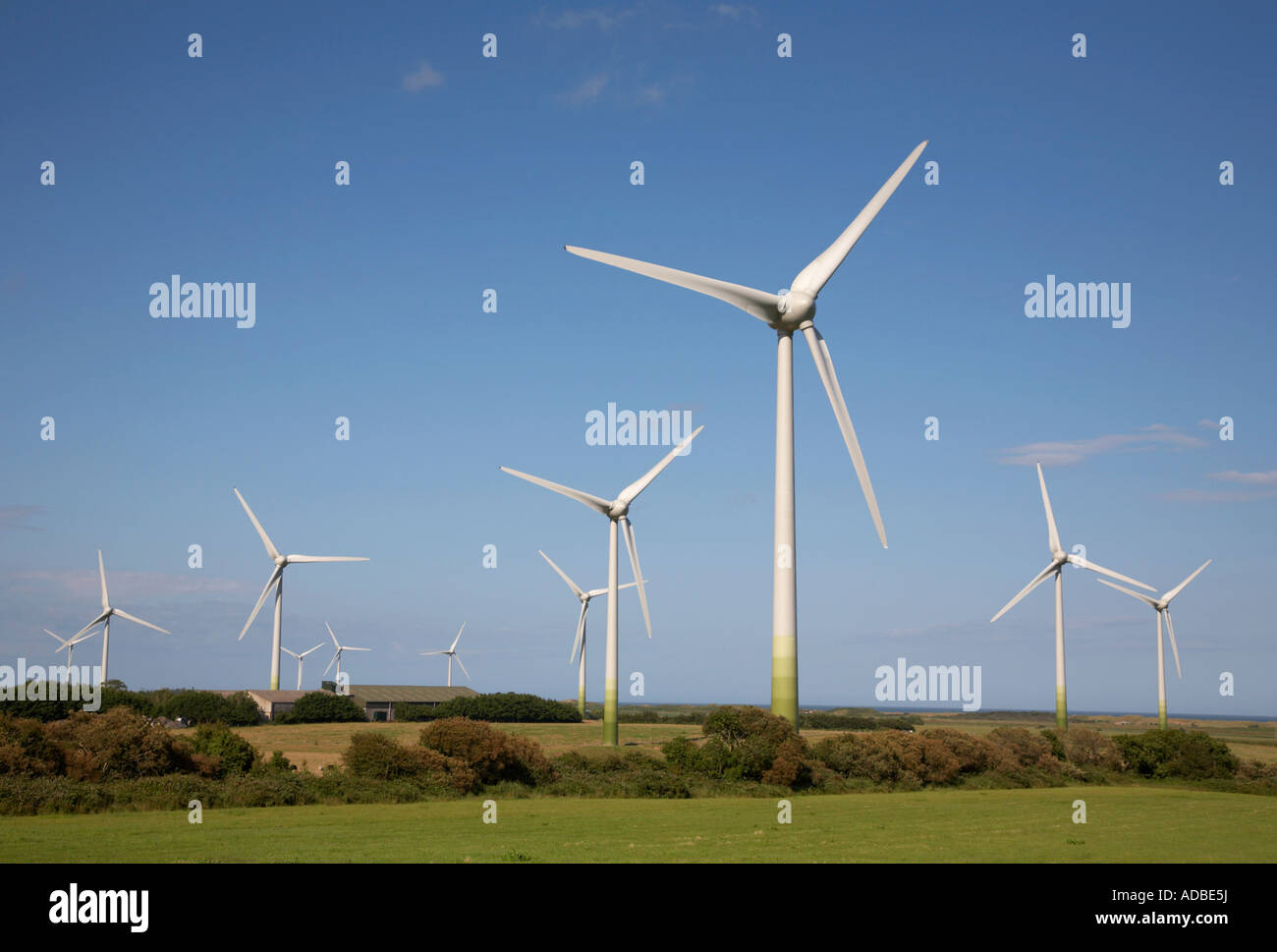 11 wind turbines and farm outbuildings on wind farm against blue cloudy sky and green fields in county wexford ireland - Stock Image