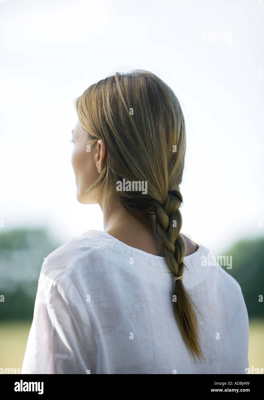Woman outdoors, hair braided, rear view - Stock Image