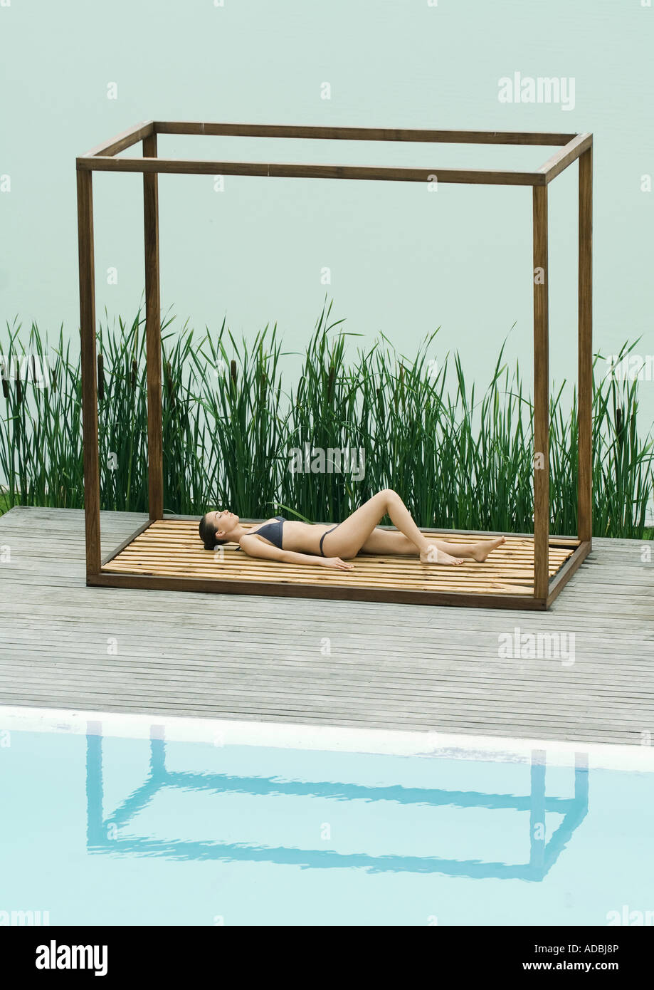 Woman wearing bikini, lying on back in square structure between lake and pool - Stock Image