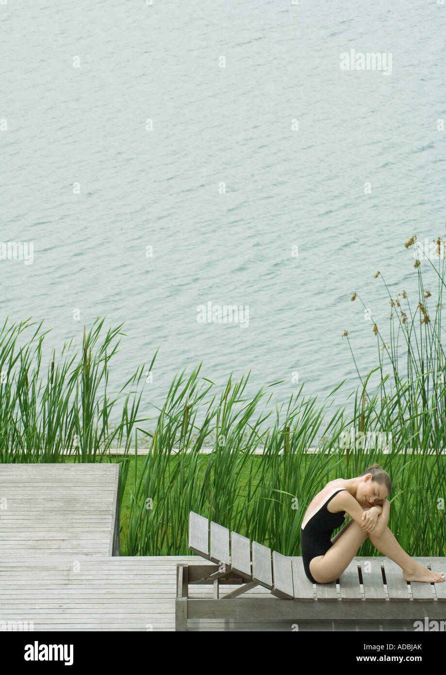Woman sitting on lounge chair next to lake, hugging knees, resting head on arms - Stock Image