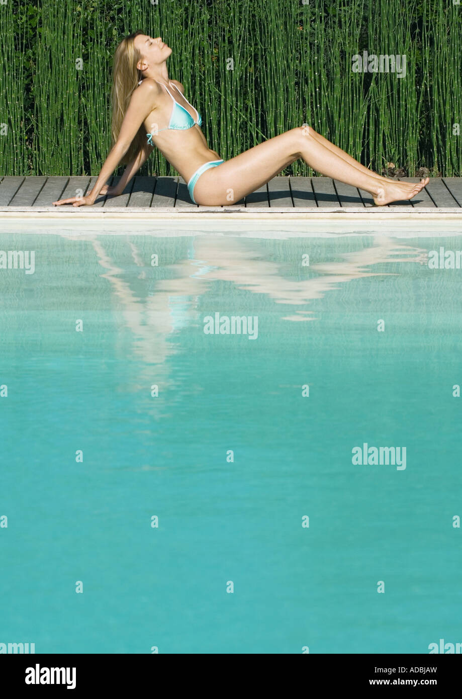 Woman sitting by edge of pool, leaning back with knees up, eyes closed, full length - Stock Image