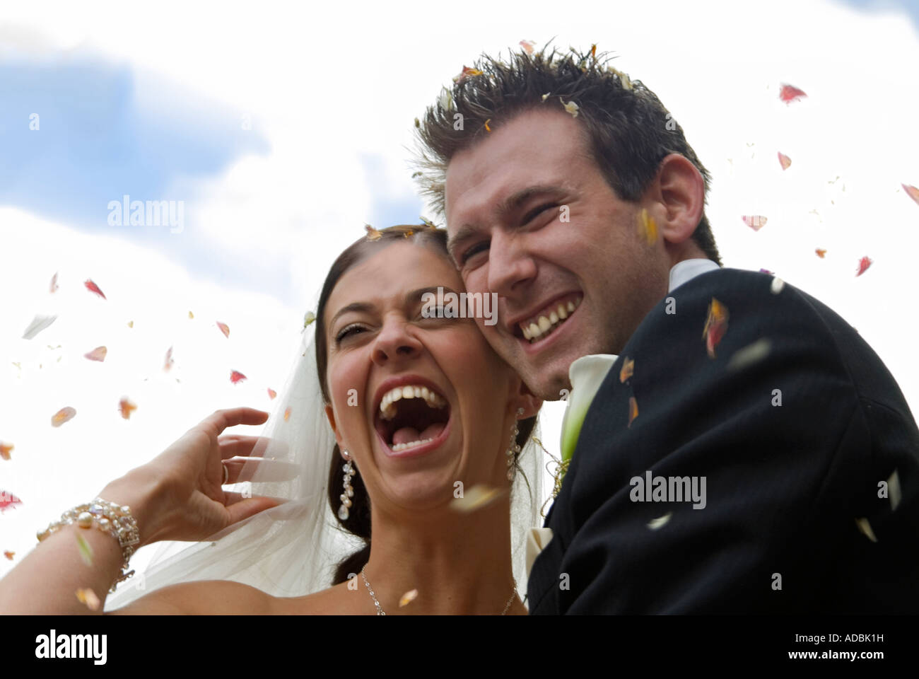 Horizontal portrait of the happy bride and groom at their wedding, traditionally having confetti thrown over them - Stock Image