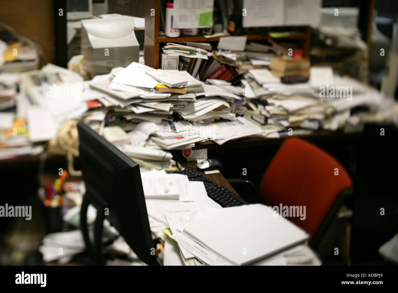A messy desk with lots of paperwork - Stock Image