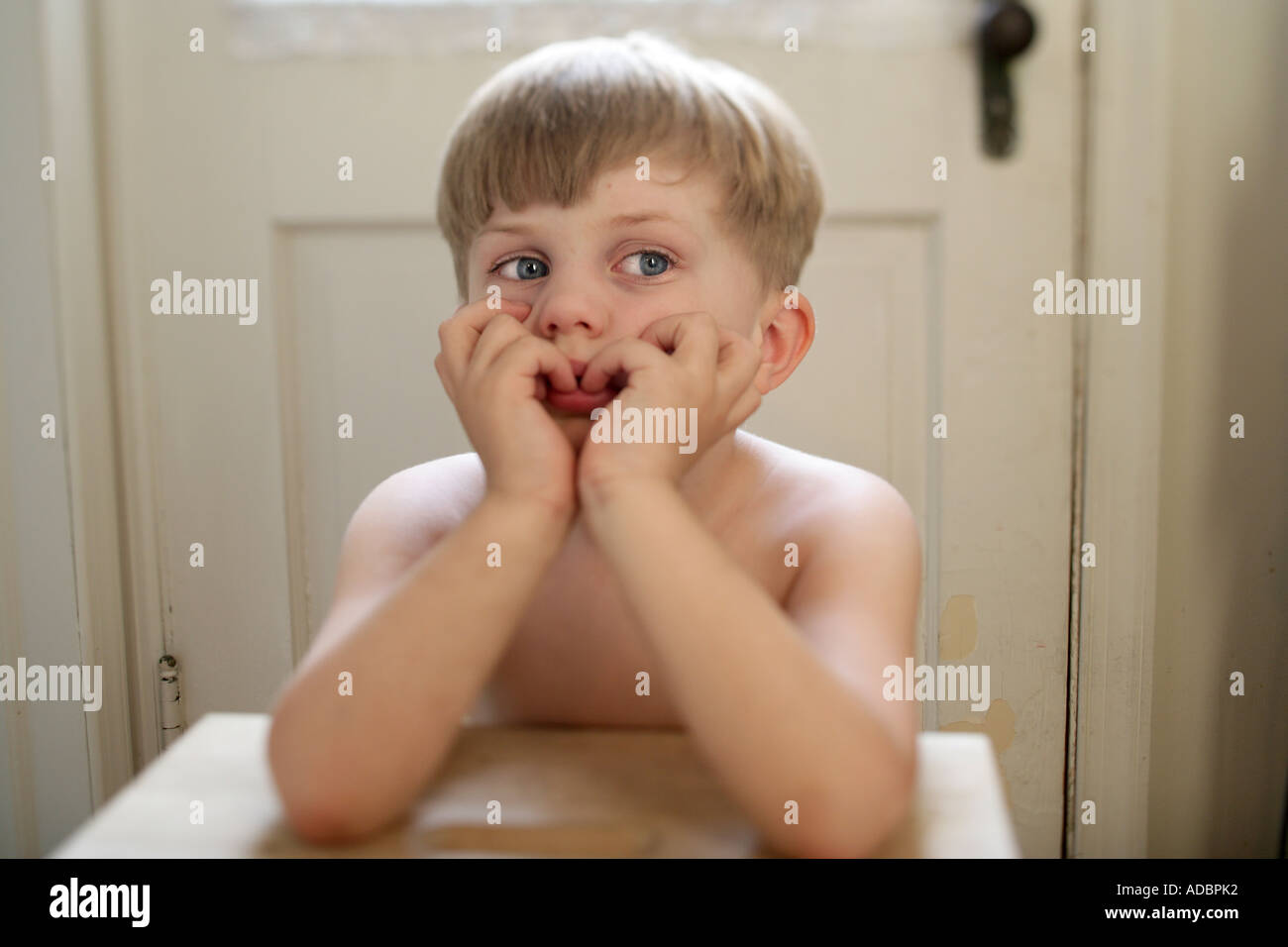 A bored Child sitting at small table looking unhappy and depressed - Stock Image