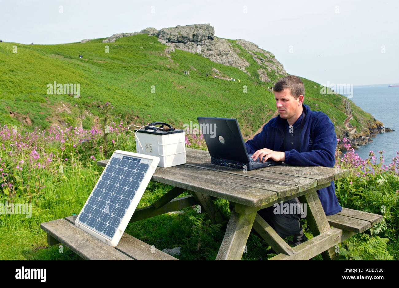 Resident warden at Skomer Island Pembrokeshire Wales UK using his laptop while charging battery with a solar panel - Stock Image