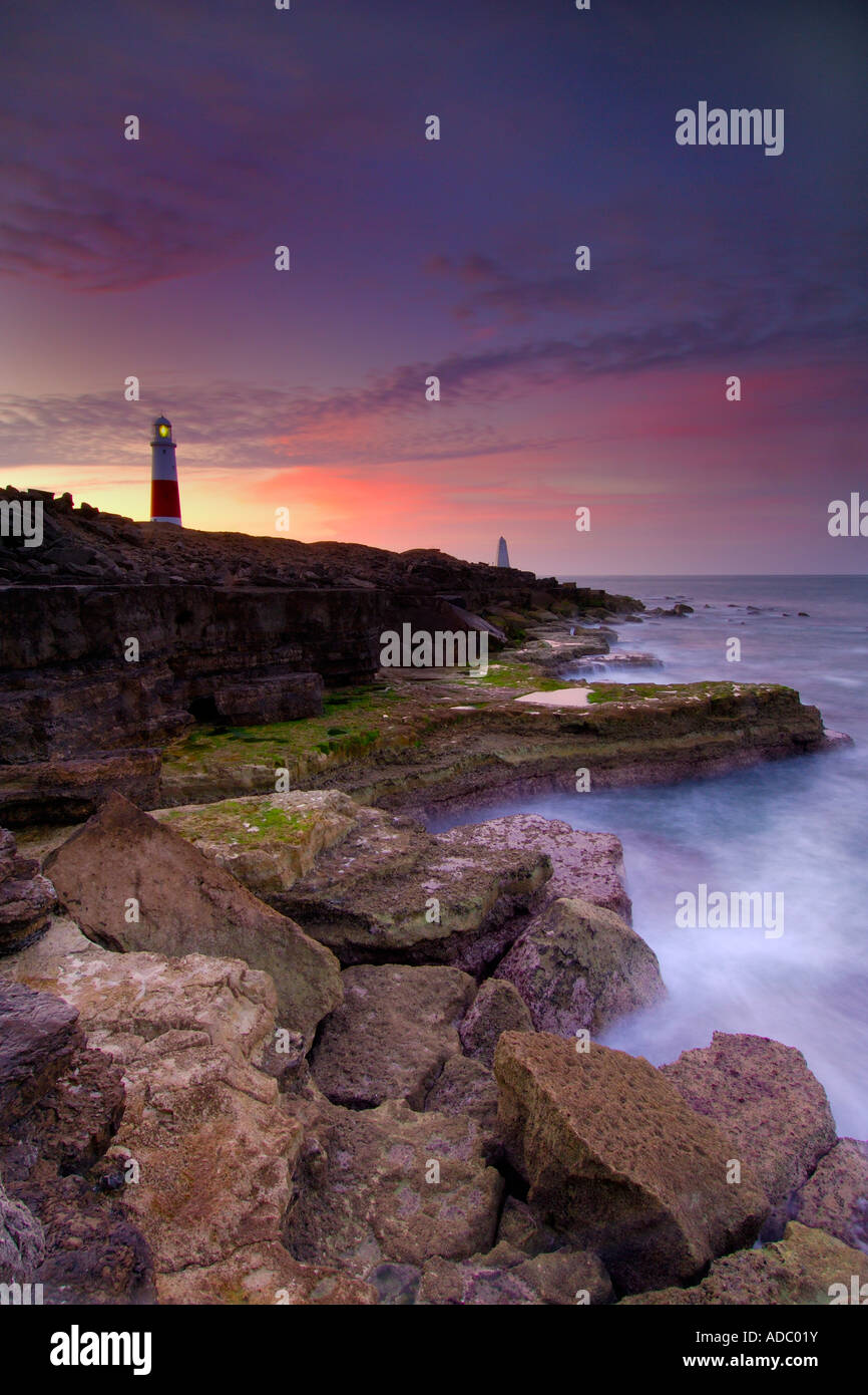 Portland Bill lighthouse just before dawn with the sea at low tide swirling around the treacherous headland rocks - Stock Image