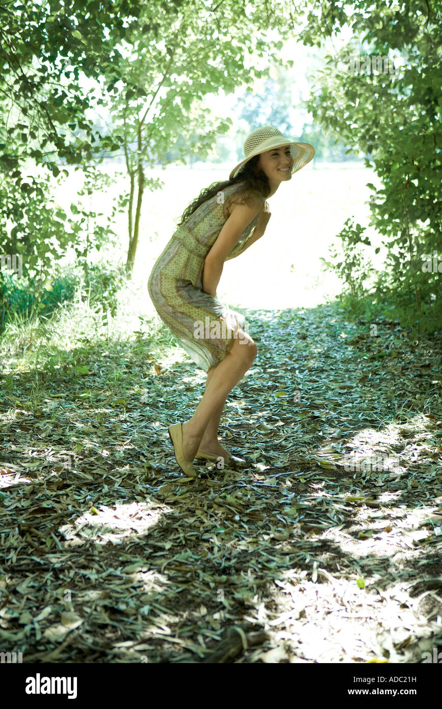 Young woman wearing sundress and sun hat in woods, bending over, full length - Stock Image