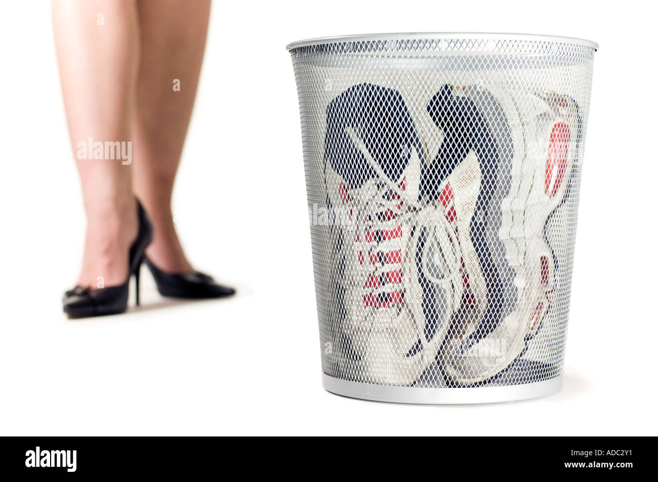 A woman discarding her training shoes for high heels - Stock Image