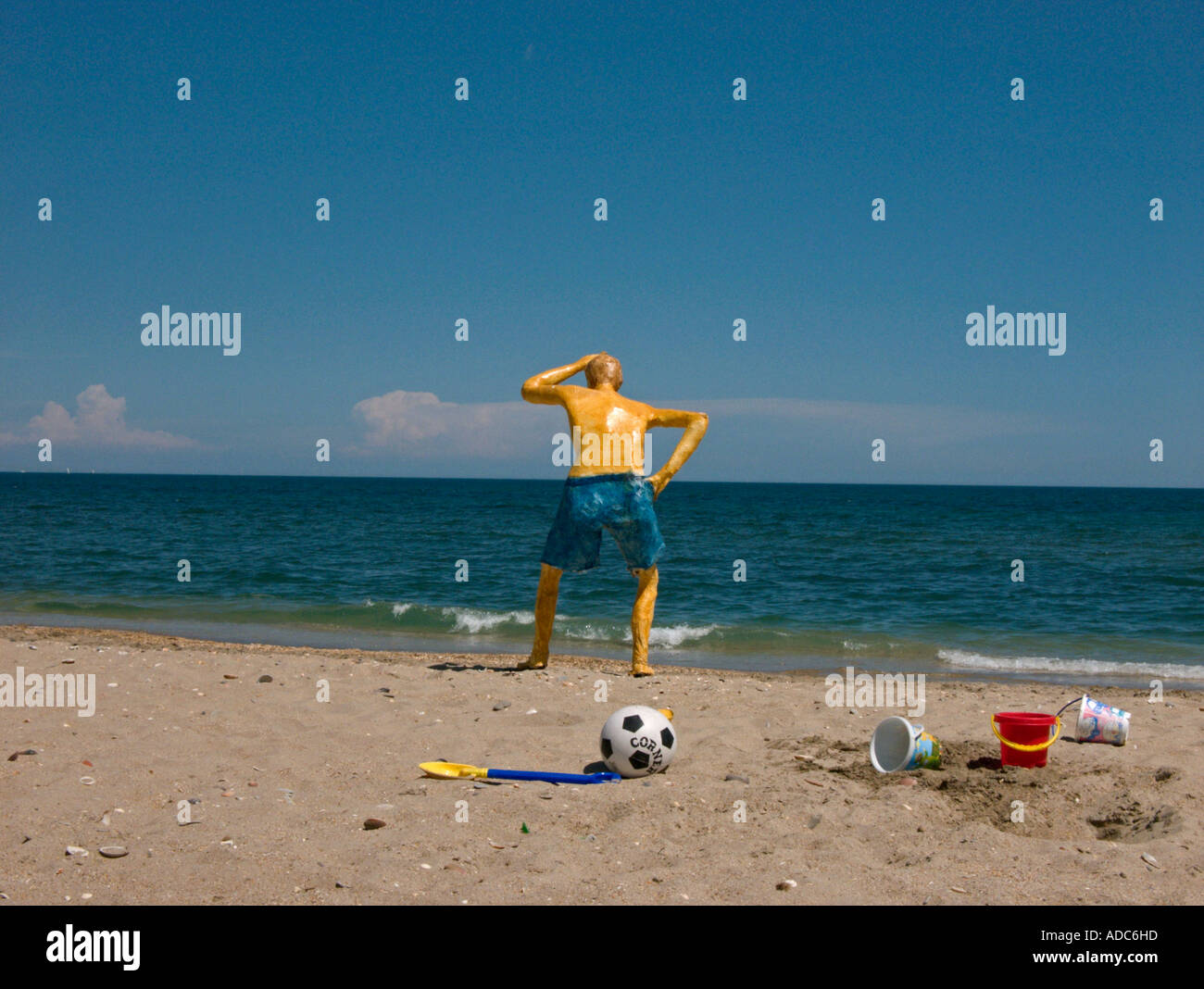 a sculpture of a man in shorts stands on a beach  looking out to sea surrounded by buckets, spades and a football - Stock Image