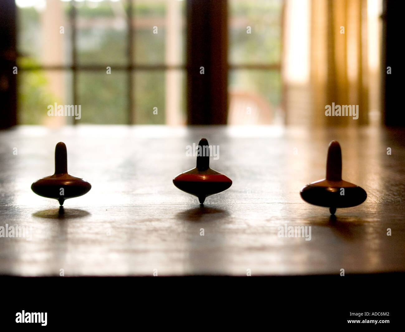 three spinning tops spinning in line on kitchen table - Stock Image