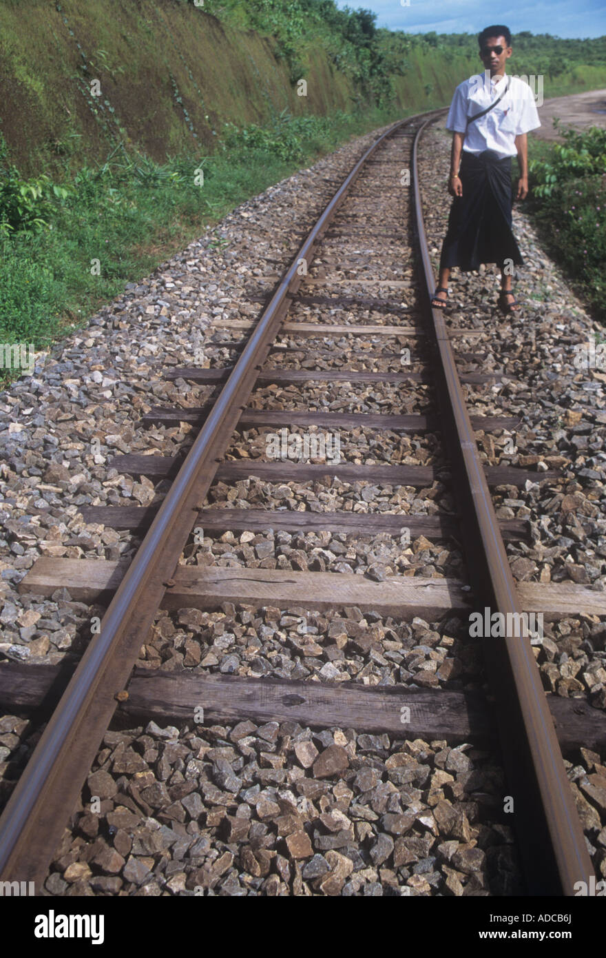 Burmese man stands beside the `Death Railway` built by POW`s in Japanese labour camps, completed 1943. - Stock Image