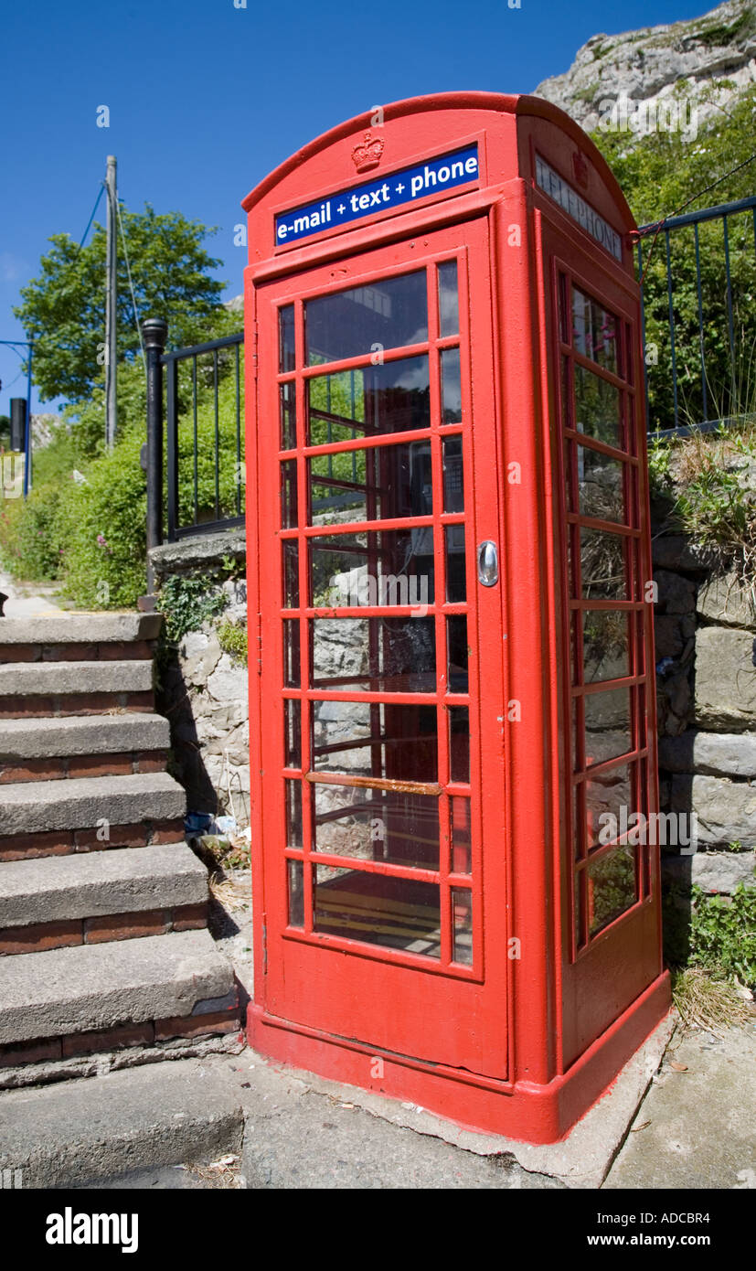 Traditional red telephone box enabled with e mail text and phone services Llandudno Great Orme Wales UK - Stock Image