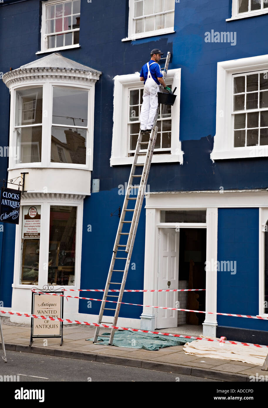 Main Using A Ladder Painting Outside Wall Of House