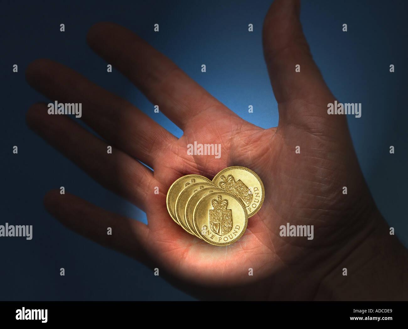 hand holding UK Pound coins Stock Photo