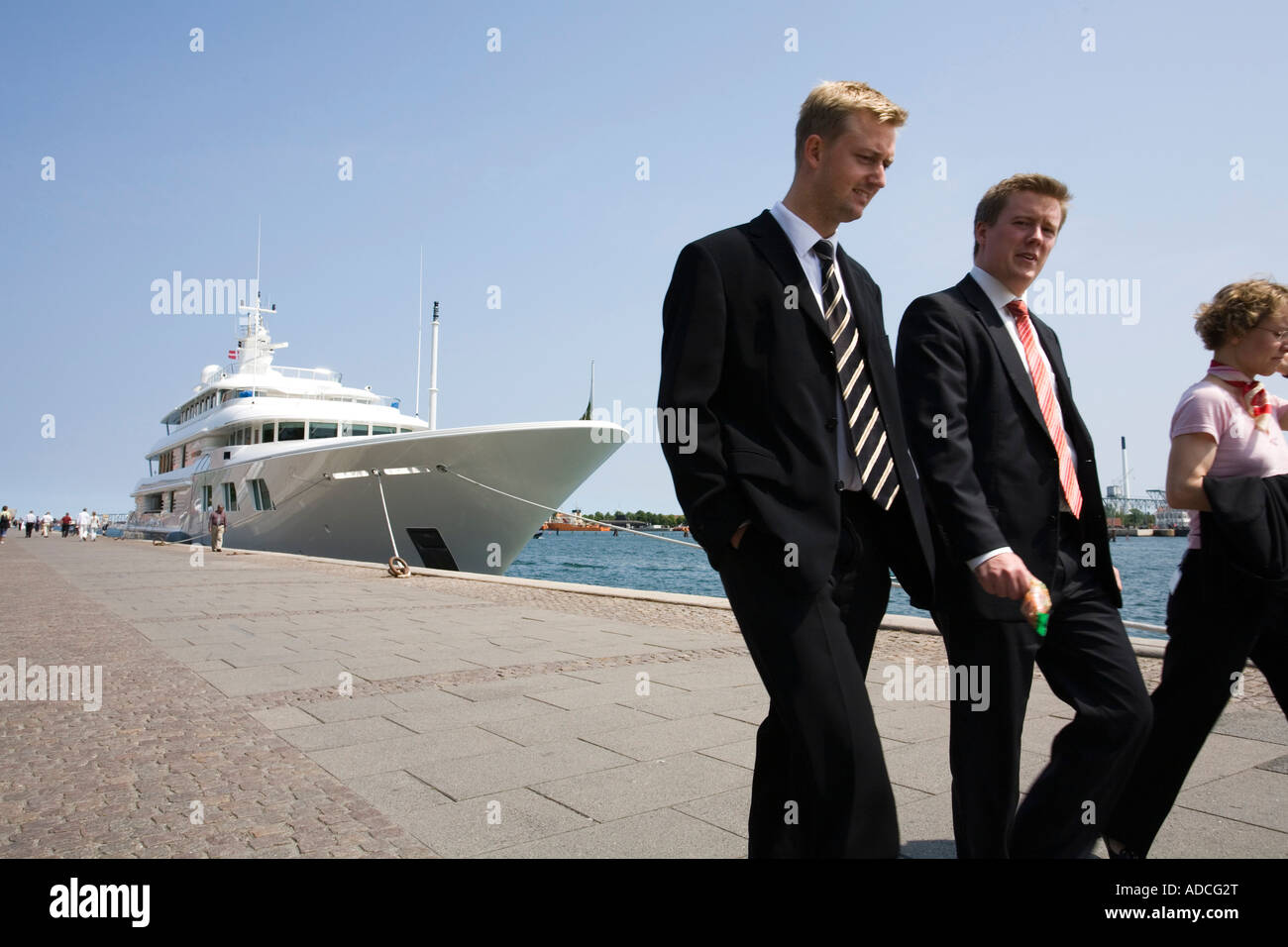 Business people walk past a luxury yacht moored at Copenhagen harbour - Stock Image