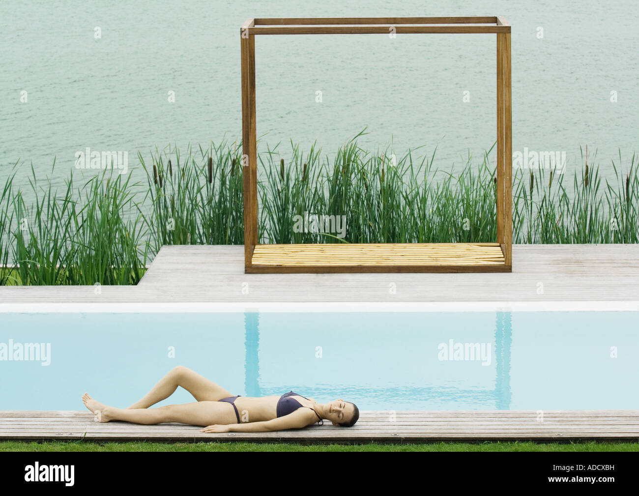 Woman lying on deck near pool, lake in background - Stock Image