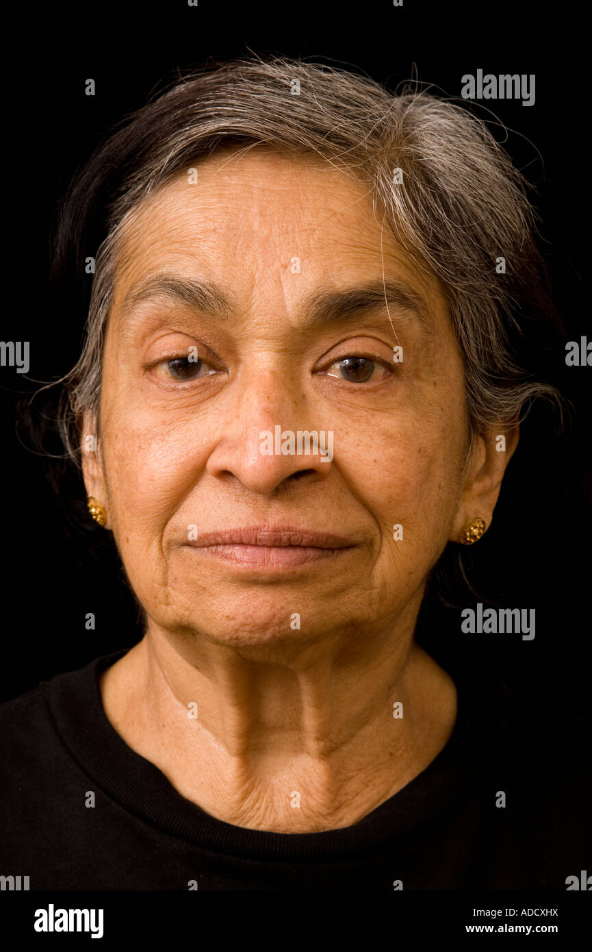 Head shot of an elderly Indian woman with greying black hair - Stock Image
