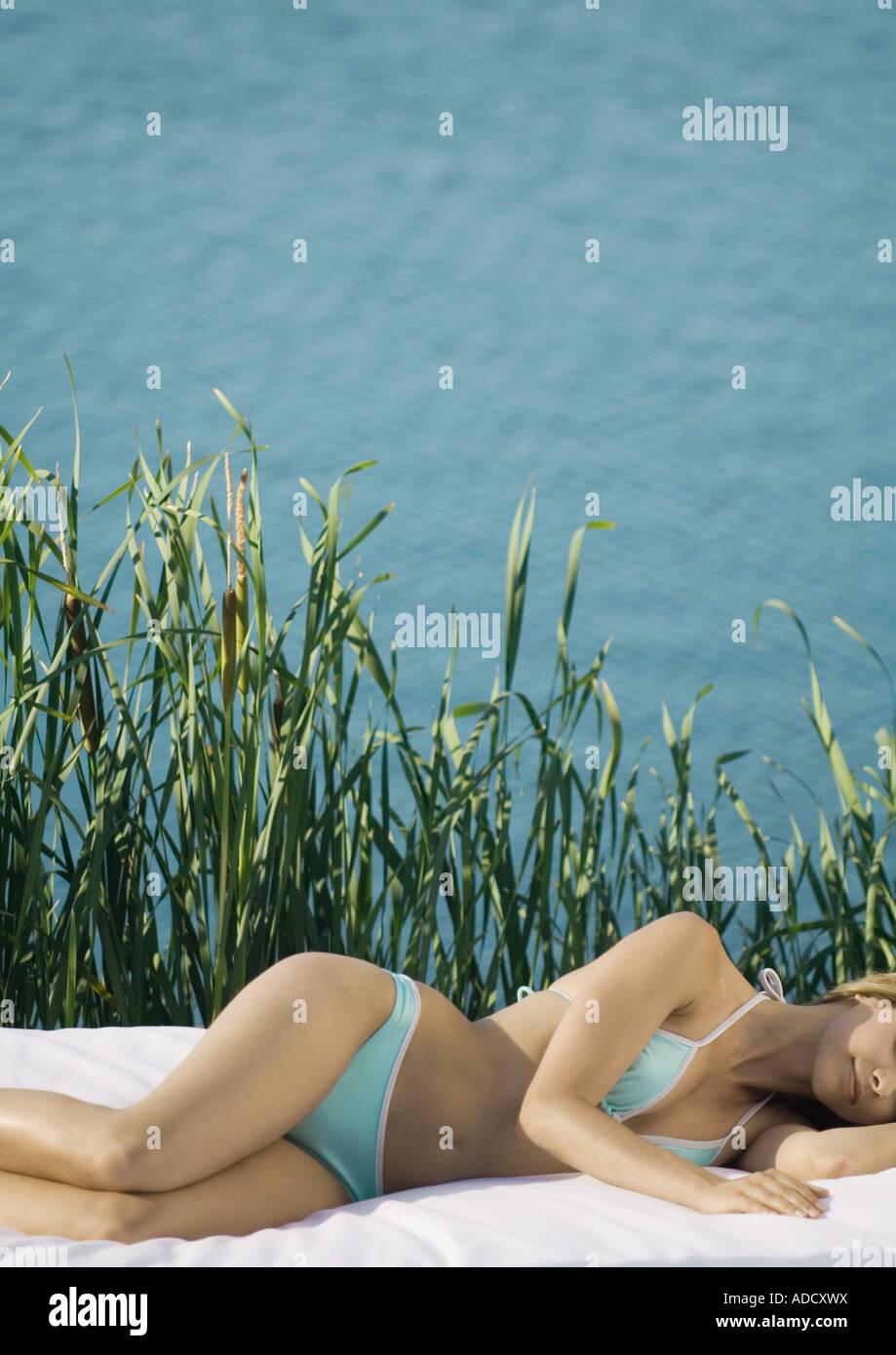 Woman in bikini lying on side, lake in background - Stock Image
