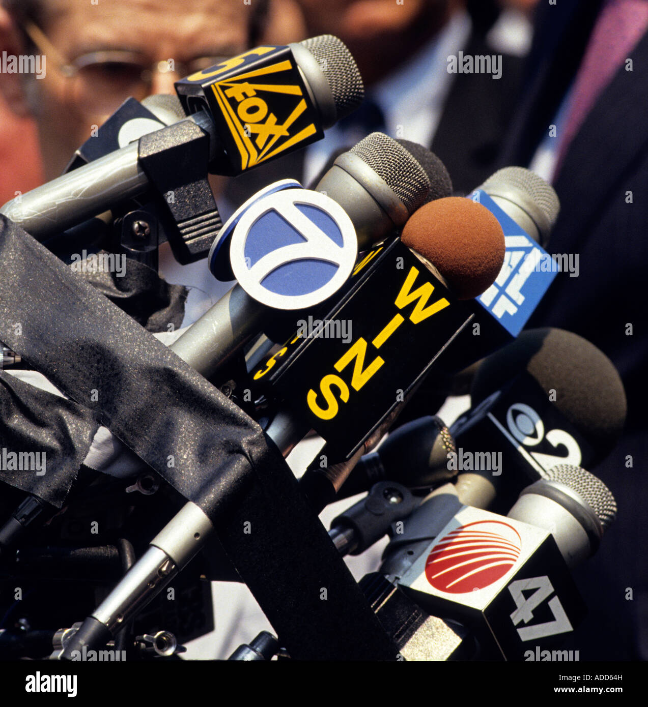 Microphones from media outlets are bundled to a stand during an outdoor press conference - Stock Image