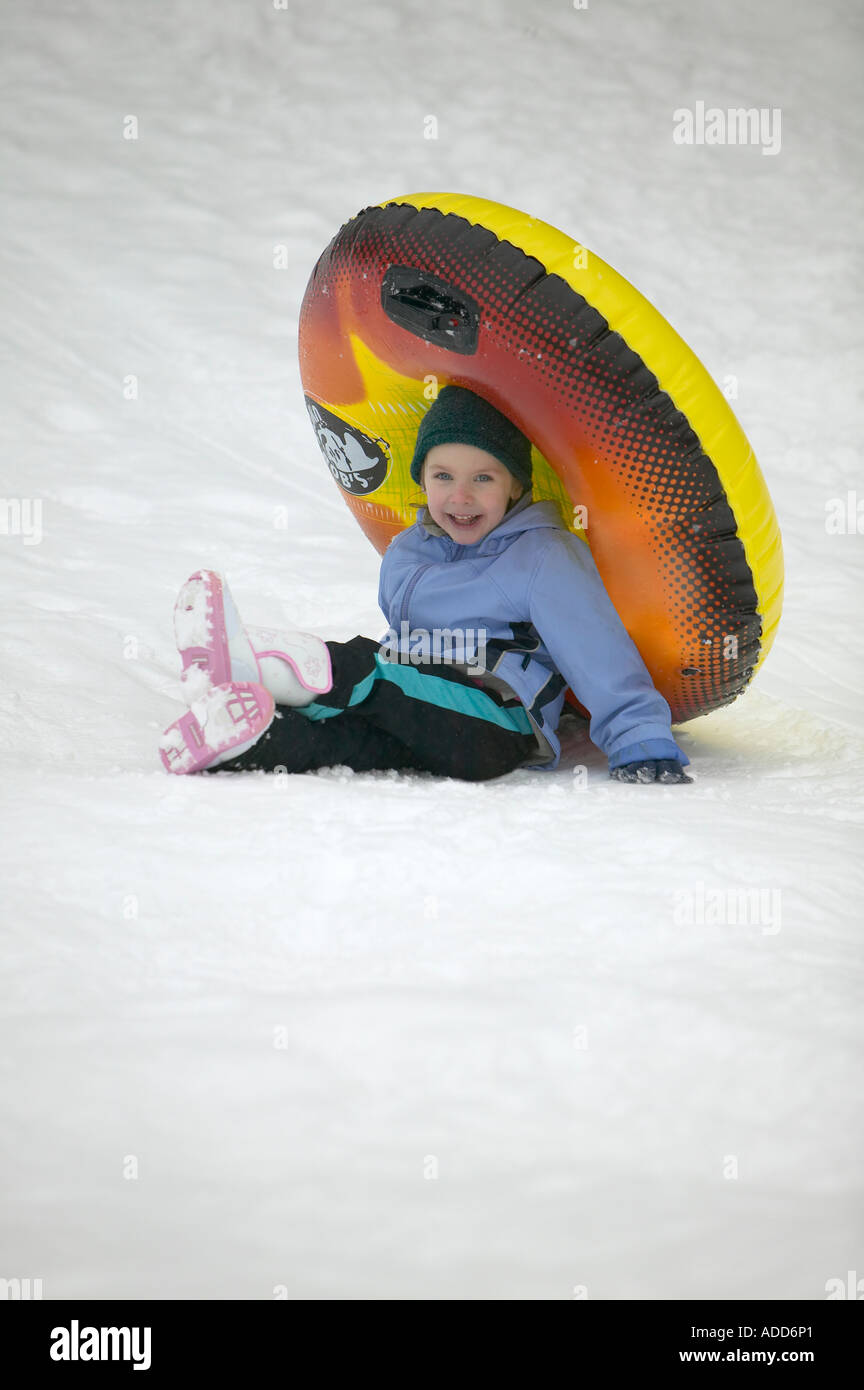 Good natured young girl fell while tubing down a snowy hill in North Carolina USA - Stock Image
