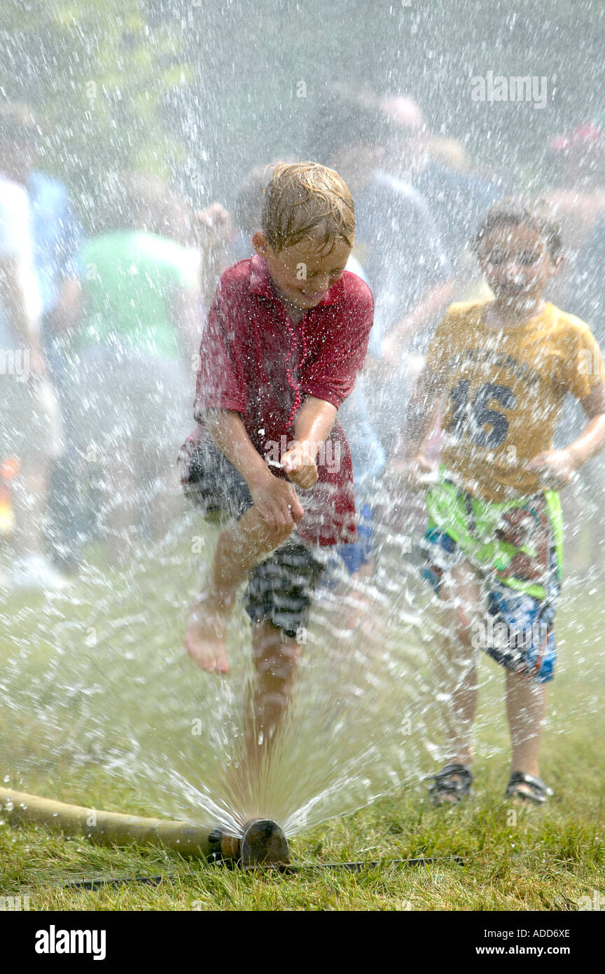 Blonde-haired boy gleefully leaps through firehose spray at 4th of July celebration; a second boy watches - Stock Image