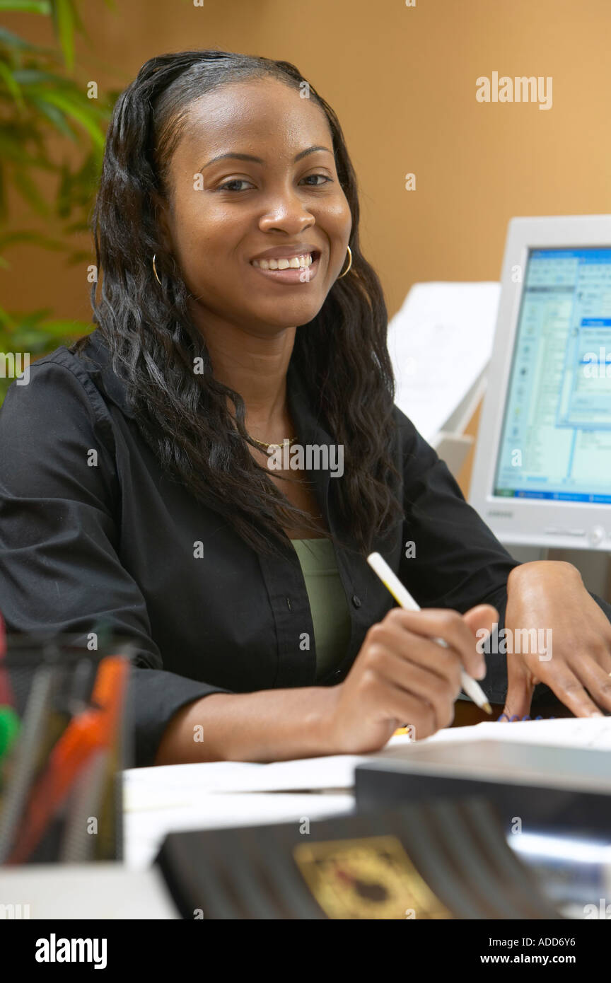 Late 20's African American female in office setting smiling with pen in hand at desk; computer screen in background - Stock Image