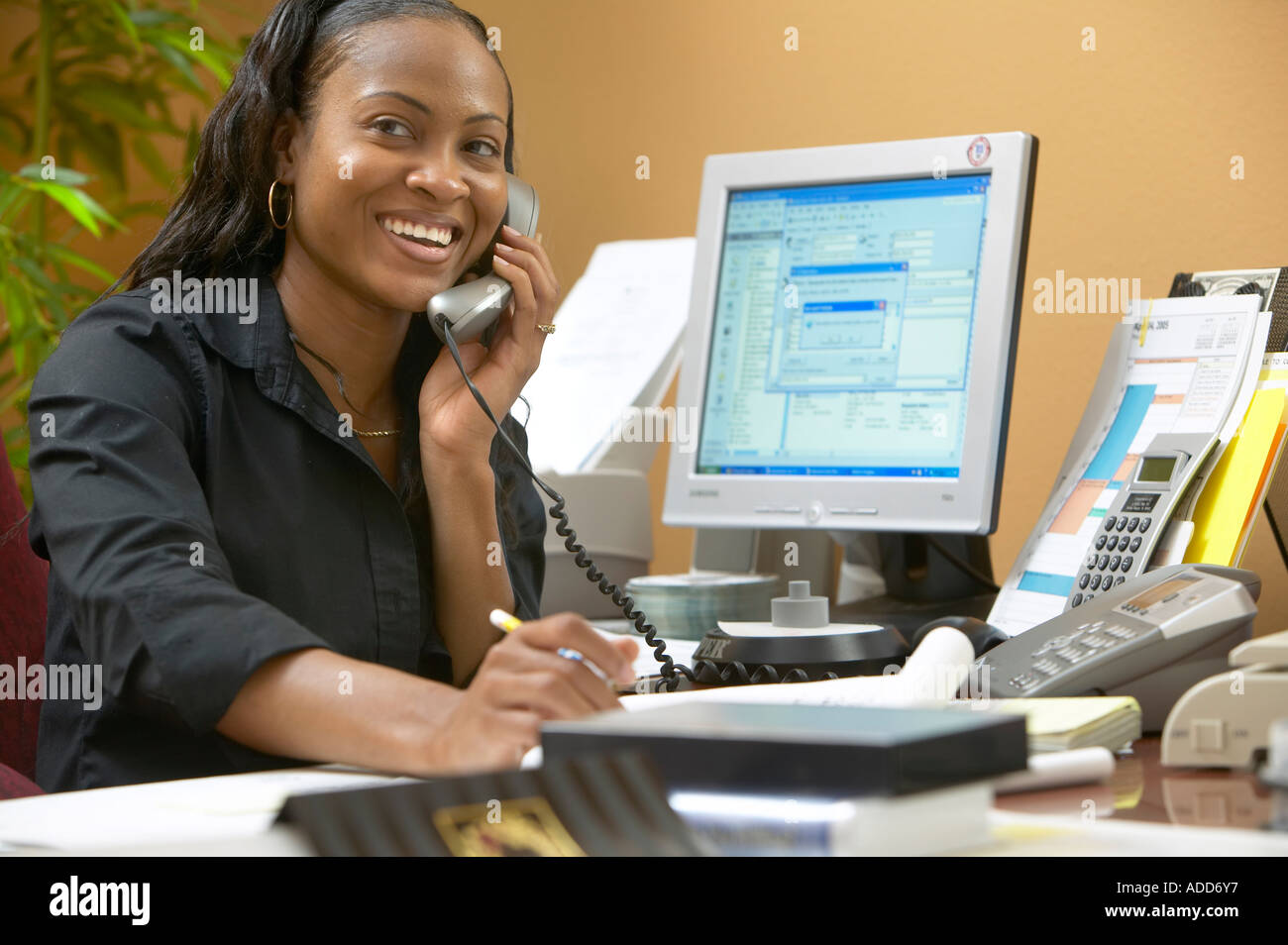 Late 20's African American female at desk in office setting smiling and talking on phone ; computer screen on desk - Stock Image