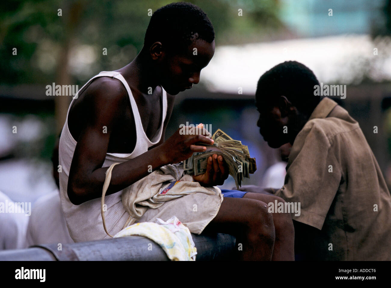 Liberia - Young trader sits on a pipe counting his money in Graystone displaced persons camp in the capital Monrovia - Stock Image