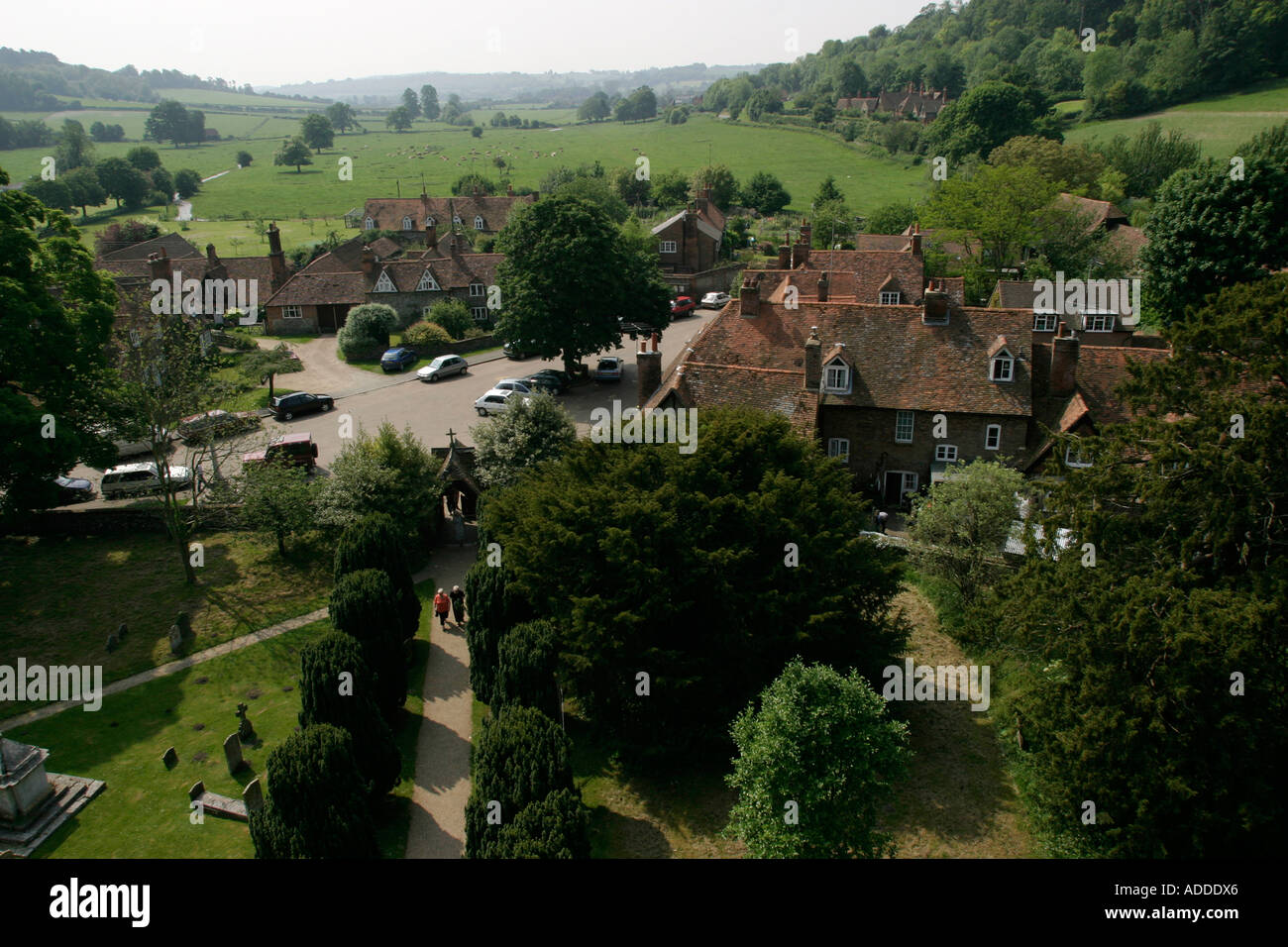High view from the clock tower of  two people walking to church in Hambleden village. - Stock Image
