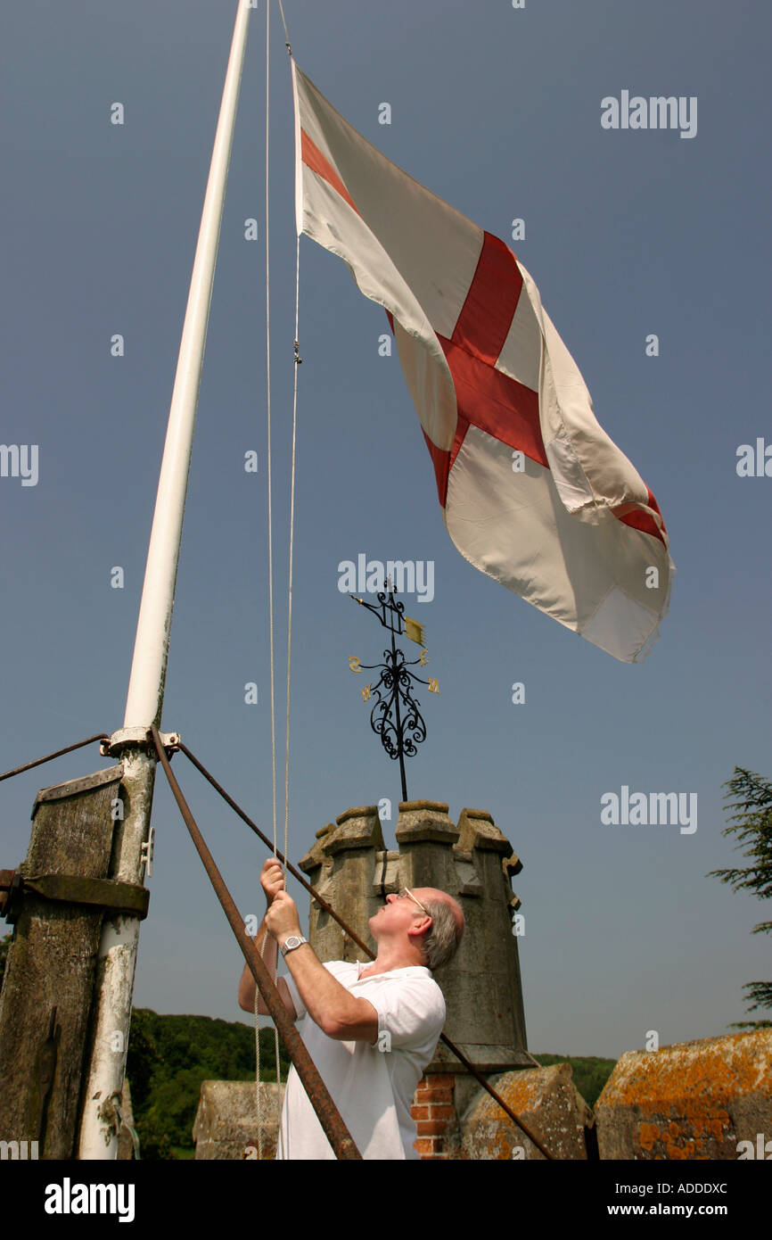 Nigel Hoppett raises the St Georges flag on the top of the Hambleden's St Mary the Virgin chuch. - Stock Image