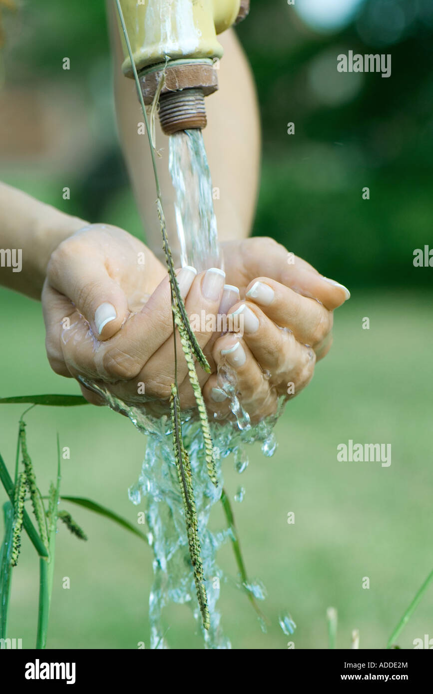 Woman cupping hands under outdoor faucet, close-up, cropped view of hands - Stock Image