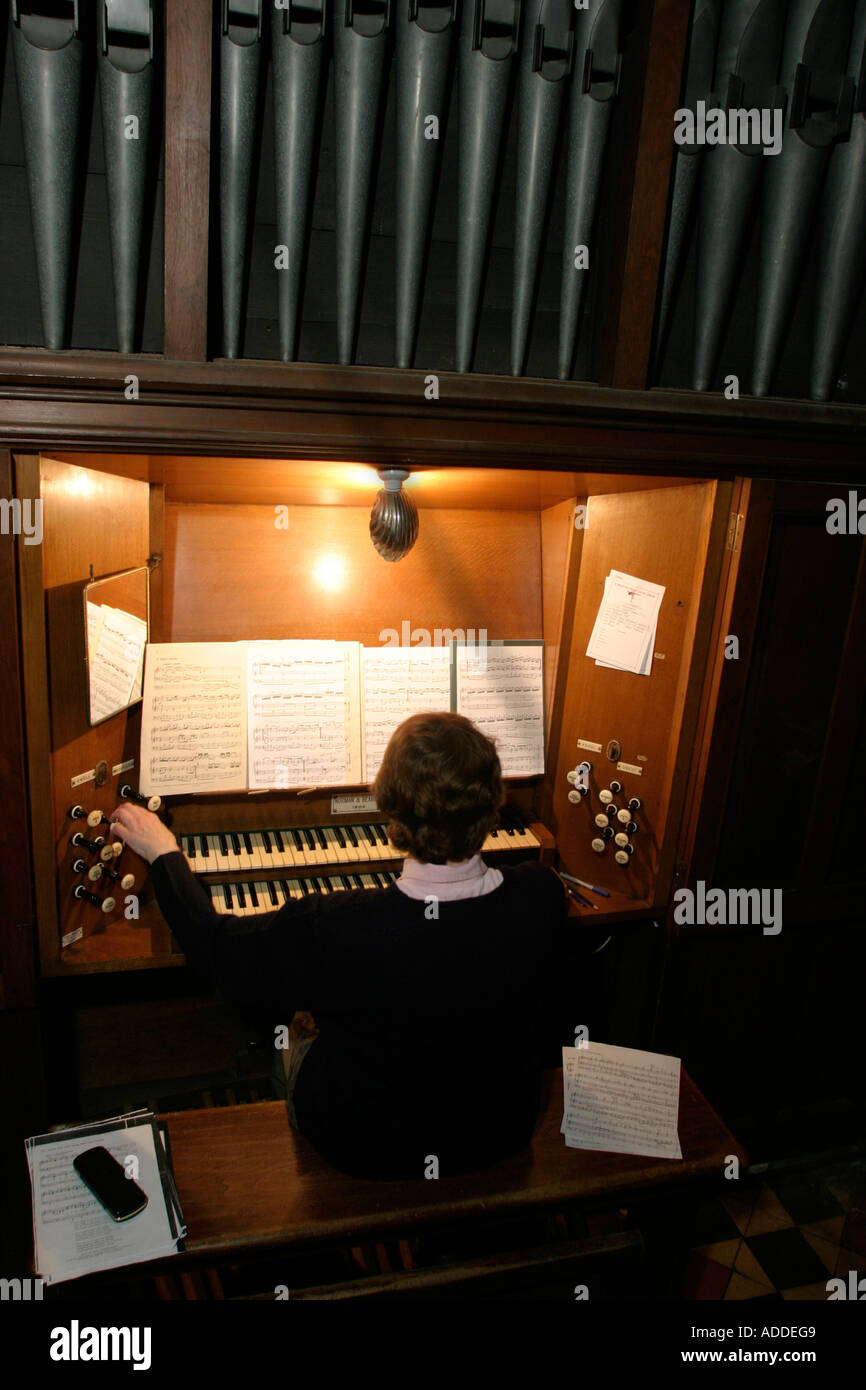Hambleden village;  Christine Wells who plays the church organ for St Mary the Virgin church services practices for a recital. - Stock Image