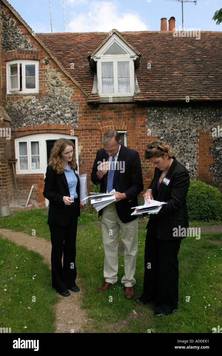 Viewer's agent  (centre) and estate agents in Hambleden village on a viewing day - the village and Estate are for sale. - Stock Image
